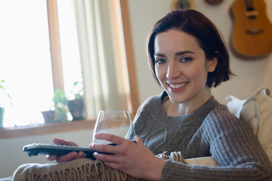 Woman at home with glass of wine and remote control