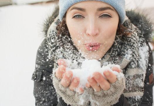 Woman blowing snow towards camera