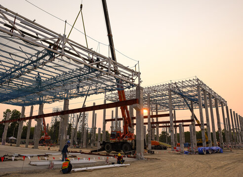 Construction workers are working at height above roof to instrallation accessory steel structure roof truss at construction site factory project during sunset time