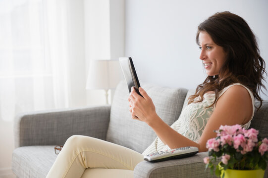Young woman on sofa reading on digital tablet