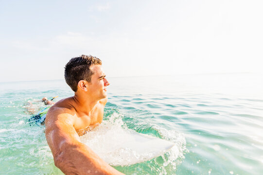 Young surfer paddling