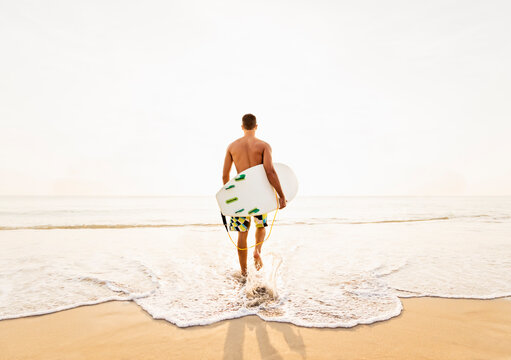 Rear view of surfer on beach