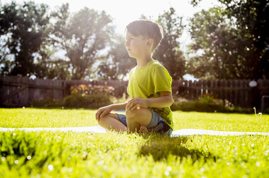 Boy (6-7) sitting in grass