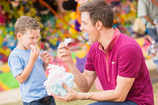 Happy father with son (4-5) in amusement park eating cotton candy