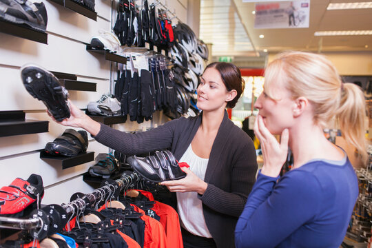 Sales clerk showing sports shoes to customer