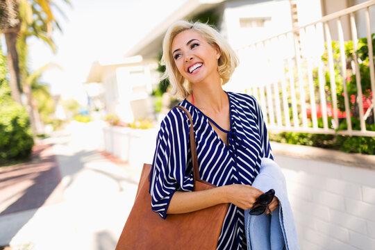 Woman wearing striped blouse walking street and smiling