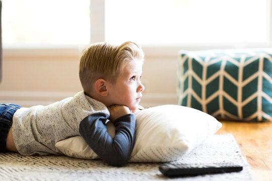 Boy (4-5) watching tv in living room