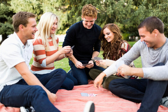 Friends playing cards in park