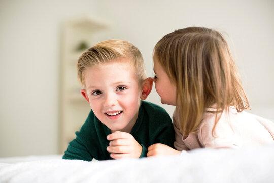 Siblings (2-3, 4-5) whispering in bedroom
