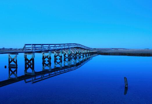 Bridge reflecting in water, blue image
