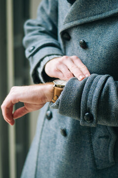 Young caucasian guy in coat looking at his watch