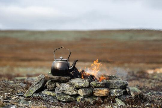 Camping kettle near camp fire. Camping place in wild. Wonderful atmospheric background of campfire. Beautiful flame of small magic bonfire. Lapland.