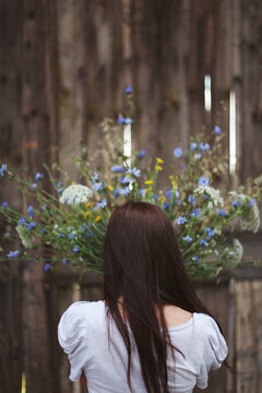Rear sight of young brunette holding mixed wildflowers bouquet in front of old wooden wall