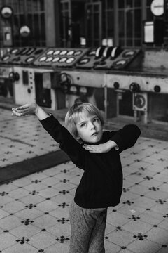 A cute boy child dances in a disused power station.