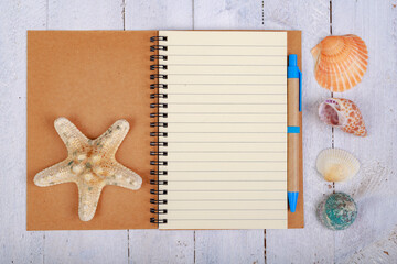 Notebook for writing your vacation memories. A blank sheet and seashells from the seaside.