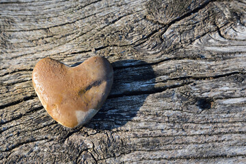 A pebble in the shape of a heart with water droplets lies on old, weathered wood
