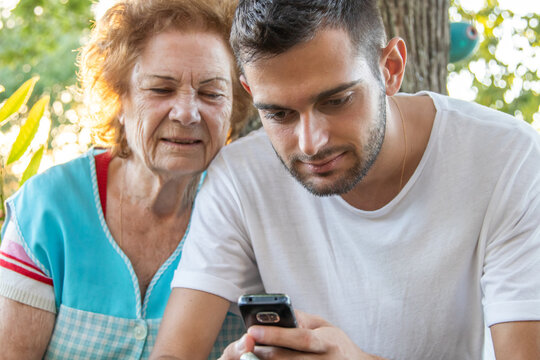 young man teaching senior woman to operate with smartphone