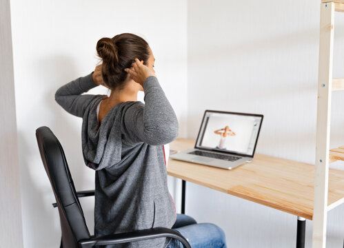 Woman doing stretching yoga at her office by online sport video. Fitness at work.