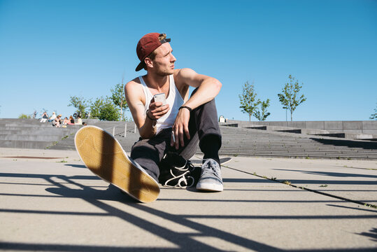 Skater is having a break - checking facebook with cell