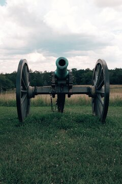 An old antique historic Civil War cannon in a field of green grass and blue skies overhead