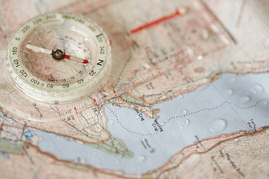 Rain droplets on a waterproof map and compass.