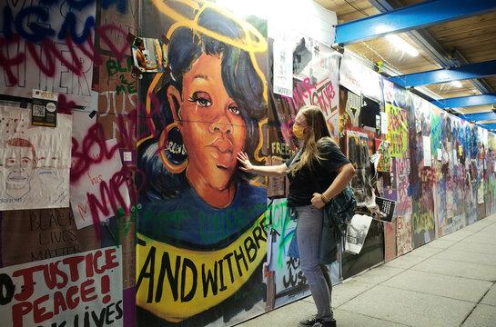 A woman touches a Breonna Taylor mural at Black Lives Matter Plaza in Washington