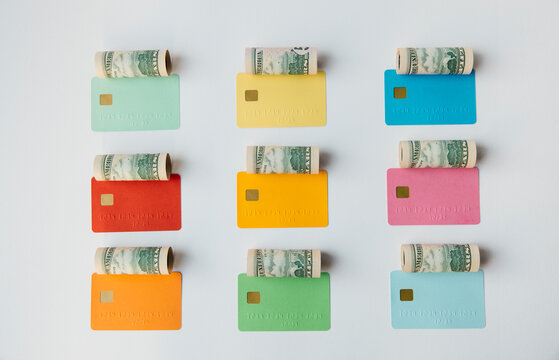 Colored credit cards with money rolls over them
