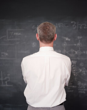 Business executive standing in front of office chalkboard