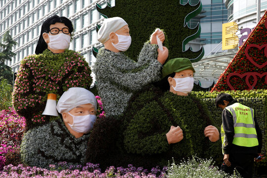Worker is seen next to a floral installation featuring medical workers, volunteers, scientists and military soldiers in the fight against the coronavirus disease (COVID-19), set up ahead of Chinese National Day on October 1, on Changan Avenue in Beijing