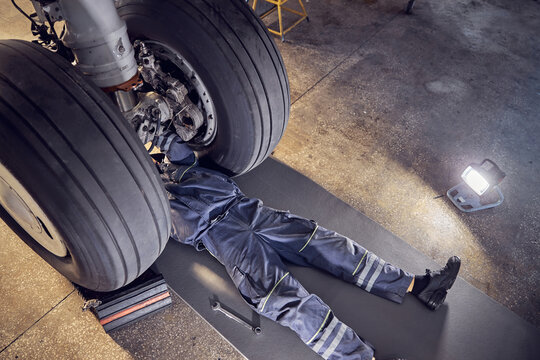 Wheels of the airplane with male mechanic in the aviation hangar