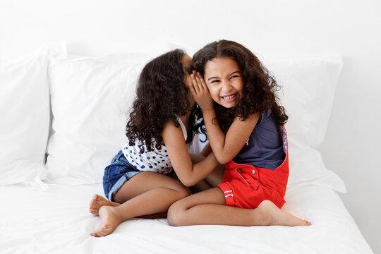 Smiling little girls whispering secrets on white bed