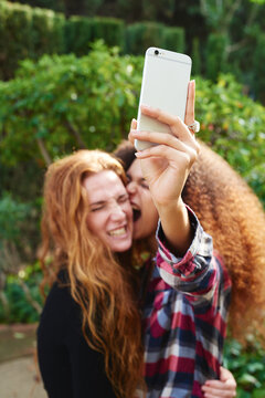 Young woman taking selfie of her girlfriend and herself