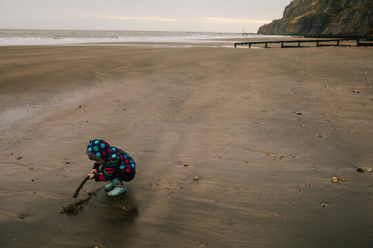 Little girl draws a line in the sand on an empty beach.
