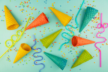 bright multicolored ice-cream waffle cones and cocktail straws on blue background with scattered confetti sugar sprinkles.