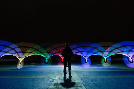 A single man silhouetted by rainbow swirls of light, standing in an empty car park