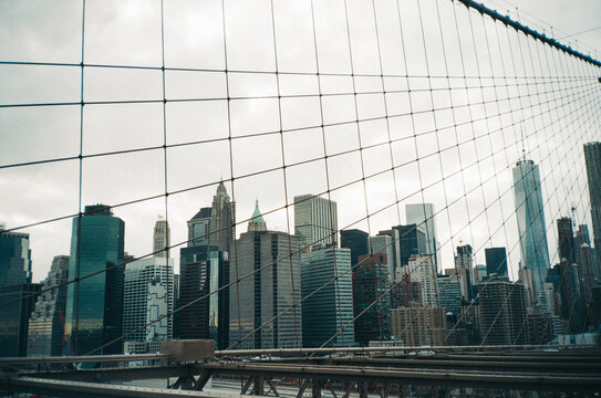 Manhattan skyline masked by cables from the Brooklyn Bridge
