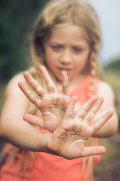 girl showing hands covered in gold glitter