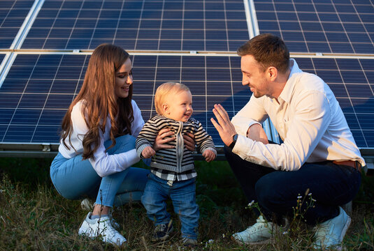 Dad, mom and baby on the background of solar panels on a warm day. The concept of family warmth and comfort in the modern world with continuously advancing technology