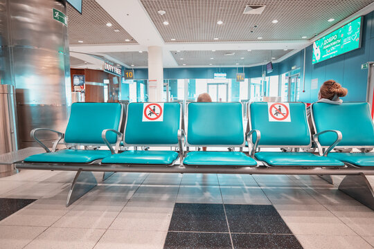 03 September 2020, Moscow, Russia: Signs on the seats at the airport draw the line between safe and dangerous areas for Seating to comply with safe social distance. Coronavirus and covid pandemic