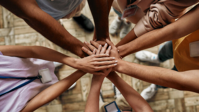Top view of diverse young volunteers putting their hands on top of each other like a real team while standing in charitable organization office