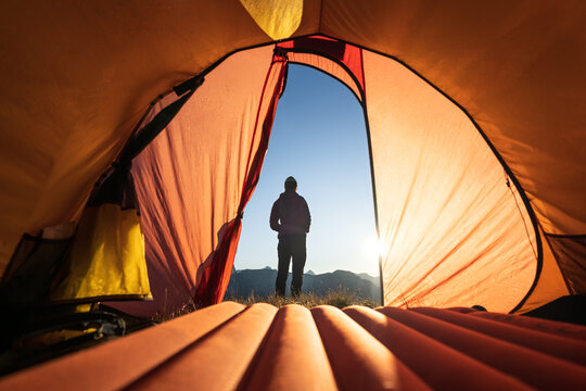 A woman looking at the sunrise in front of her tent in the mountains.
