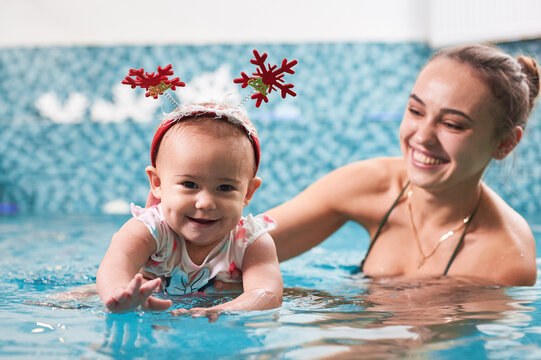 Happy baby girl with Christmas headband spending time with loving mother in swimming pool. Charming young woman helping cute child to swim and smiling. Concept of happy childhood, swimming training