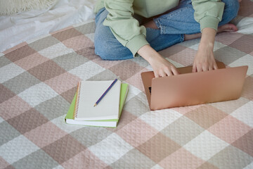 Cute teenager girl doing homework sitting on bed at home. Education, children and school concept, distance learning, self education