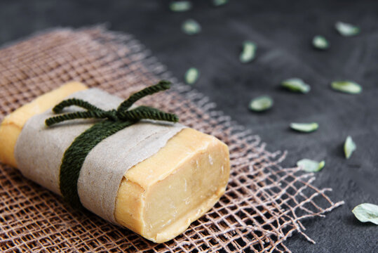 Pieces of household soap tied with jute rope, antique wooden background. Eco-friendly product - the concept of cleanliness and health.