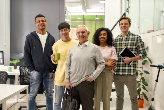 Happy diverse team of employees looking at camera while posing with senior intern, standing together in the office, Age diversity in the workplace
