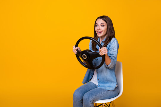 Profile photo of pretty funny lady good mood sit chair hold steering wheel ride imagine car drive license examination excited wear casual denim shirt isolated yellow color background