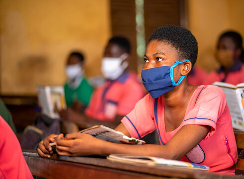 image of African lady with face mask with her colleagues blurred at background- classroom concept