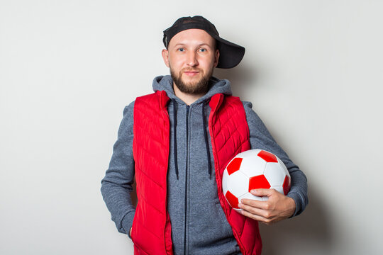 Young man in a casually dressed cap, hoodie and vest holding a soccer ball on a light background
