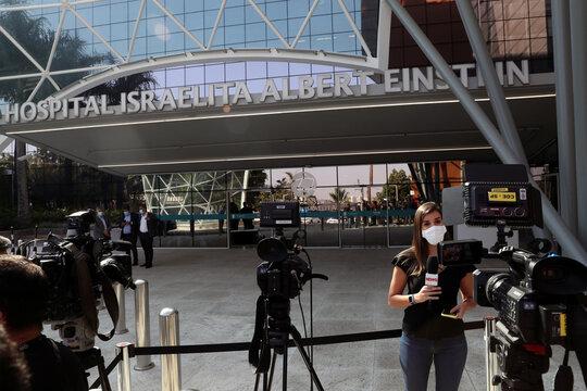 A journalist stands at the entrance of Albert Einstein Hospital, where Brazil's President Jair Bolsonaro will undergo surgery in Sao Paulo