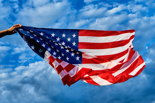 man waving an American flag on the wind